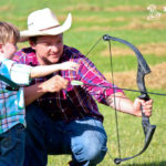 Man teaching a kid how to shoot a bow and arrow