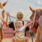 Little girl on her mom's back petting a horse