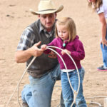 Little girl learning how to cowboy rope