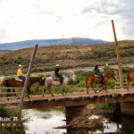 Family crossing a bridge while horseback ridding