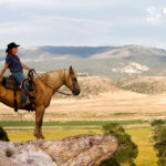 Cowgirl looking over the land on her horse